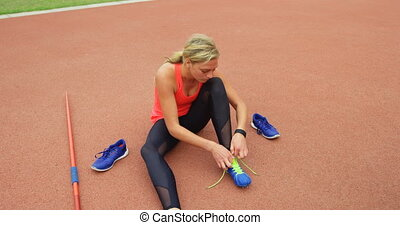 High angle view of Caucasian female athlete tying shoelaces at sport venue. She is getting ready for a javelin throw 4k