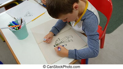 High angle view of Caucasian schoolboy drawing on notebook ...