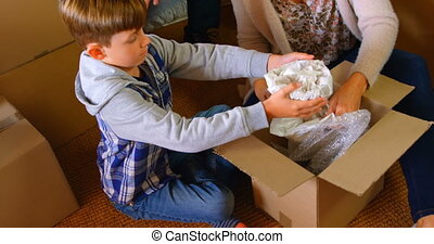 High angle view of Caucasian son helping his mother to packing belongings at home. Son putting belongings in cardboard box 4K 4k