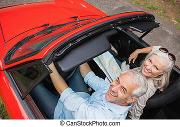 High angle view of cheerful mature man having a ride with his wife in red convertible