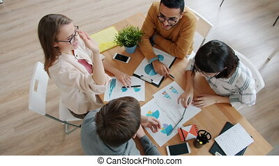High angle view of cheerful youth talking working in office then doing high-five enjoying productive cooperation. Work, business and emotions concept.