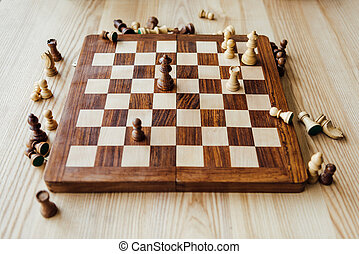High angle view of chess figures scattered on chessboard at the table
