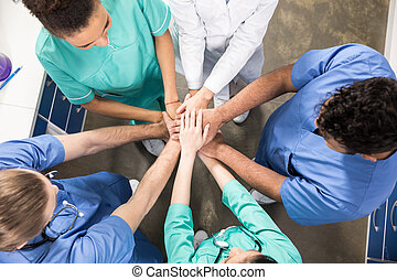 high angle view of colleagues holding hands together
