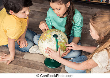 high angle view of concentrated children exploring globe in library