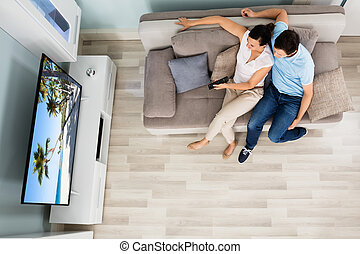 High Angle View Of Couple Watching Television - High Angle...