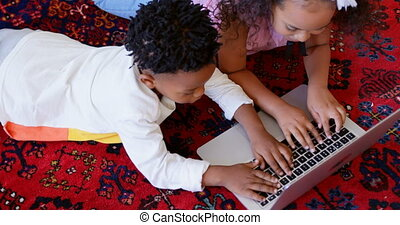 High angle view of cute black siblings using laptop in living room at comfortable home 4k