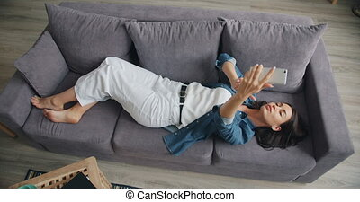 High angle view of cute girl taking selfie with smartphone lying on sofa at home