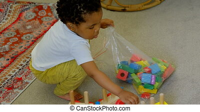 High angle view of cute little black boy playing and crouching on floor of comfortable home 4k