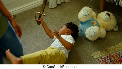High angle view of cute little black boy playing and lying on floor of comfortable home 4k