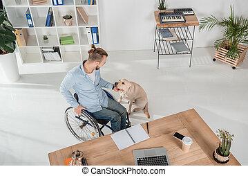 man on wheelchair petting his dog