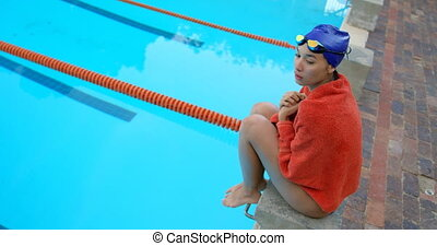 High angle view of female swimmer sitting near swimming pool...