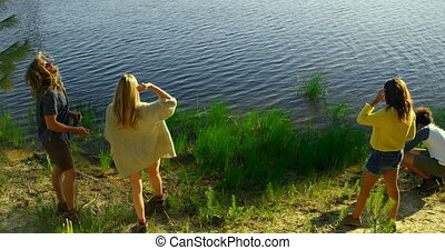 High angle view of friends having fun near lakeside 4k - ...