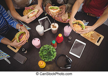 High angle view of friends holding fresh food at coffee shop