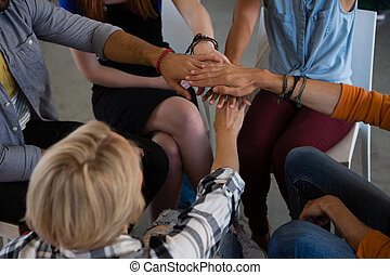 High angle view of friends stacking hands