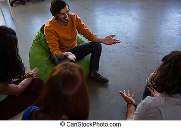 High angle view of friends talking while sitting on chair