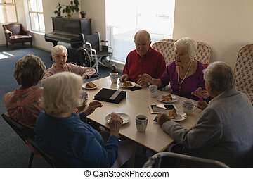 High angle view of group of senior friends having breakfast on dining table