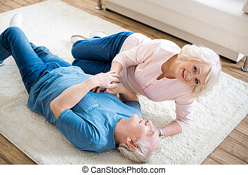 High angle view of happy senior couple lying together on carpet
