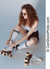 High angle view of hipster girl in sunglasses wearing roller skates sitting isolated on grey