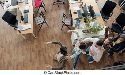 High angle view of joyful people office workers dancing in modern open space workplace enjoying corporate party. Happy employees and workspace concept.