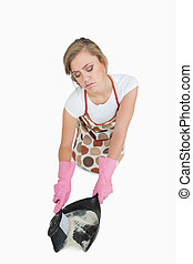 High angle view of maid using brush and dust pan over white...