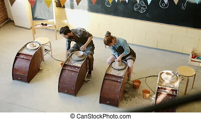 High angle view of male and female ceramists working with ...