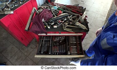 High angle view of male mechanic arranging tools in drawer...