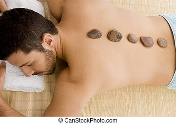 high angle view of male relaxing for hot stone treatment