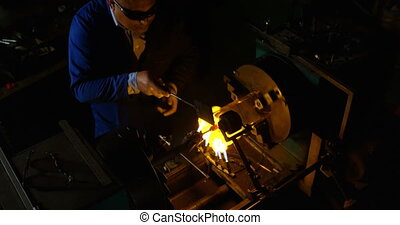 High angle view of male worker blowing glass in glass factory. Male worker heating glass 4k