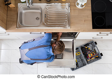 Man In Overall Repairing Dishwasher - High Angle View Of Man...