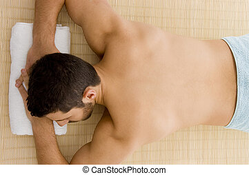high angle view of man lying down for spa treatment