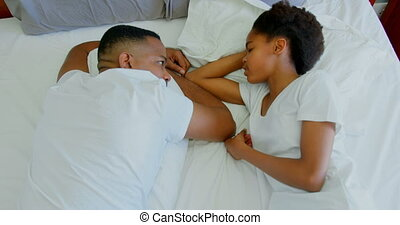 High angle view of mid adult black father and daughter relaxing on bed in a comfortable home 4k