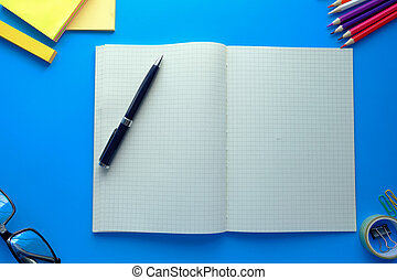 high angle view of open notepad, pen on blue background