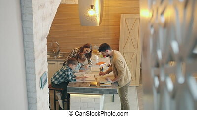 High angle view of parents caring father and mother helping cute children with homework in kitchen in modern house. People and education concept.