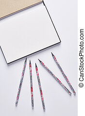 High angle view of pencils on the notebook