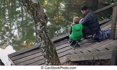 High angle view of people father and son fishing in pond in...