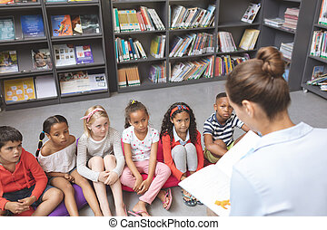 High angle view of school kids listening their teacher telling them a story