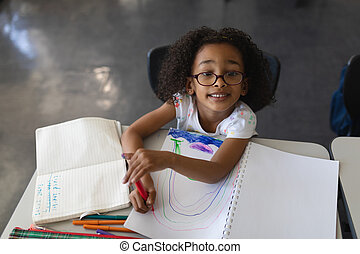 High angle view of schoolgirl drawing in book while looking at camera in classroom