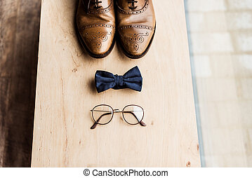 high angle view of shoes, tie bow and glasses on wooden...