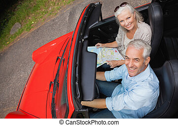 High angle view of smiling mature man having a ride with his wife in red convertible