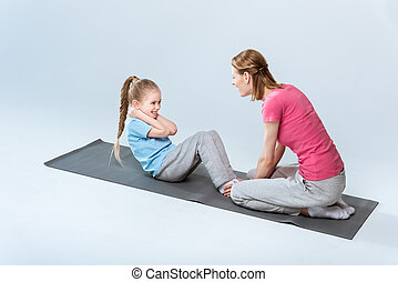 high angle view of sporty mother and daughter exercising on mats together