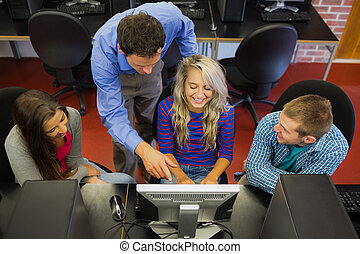 High angle view of teacher showing something on screen to students in the computer room