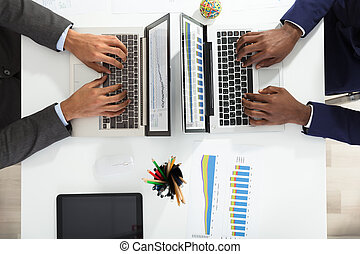 Two Businesspeople Analyzing Graph On Laptop