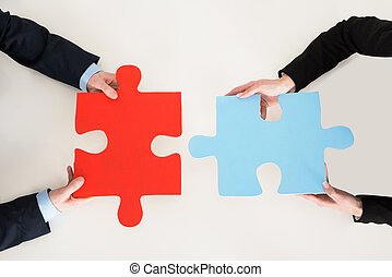 Businesspeople Connecting Puzzle Pieces