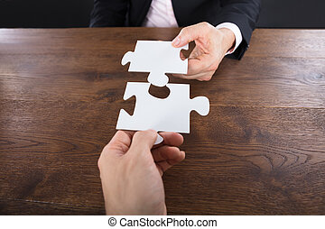 Two Businesspeople Connecting Puzzle Pieces