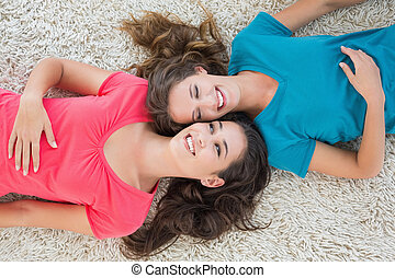High angle view of two young female friends lying on rug