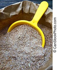 High angle view of wheat bran in a brown paper bag in closeup
