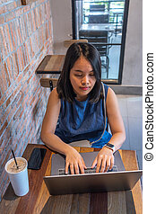 High angle view of woman using laptop at rustic cafe