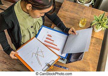 High angle view of woman working on sales chart document