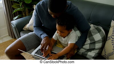 High angle view of young black father and son using laptop in living room of comfortable home 4k