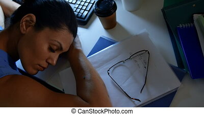High angle view of young Caucasian female executive sleeping...